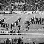 "The Million Dollar Band on the football field, forming the letters ""U"" and ""A."""