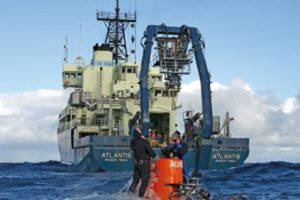 Research Vessel Atlantis and the human-occupied vehicle Alvin are shown. Divers meet the sub when it surfaces to attach it to a hoist rope and bring it back on board (Image Woods Hole Oceanographic Institution).
