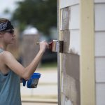 Young woman painting a building